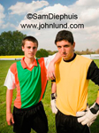 Two young adult soccer players on a soccer field. One is a goalie. Argentina futbol players.